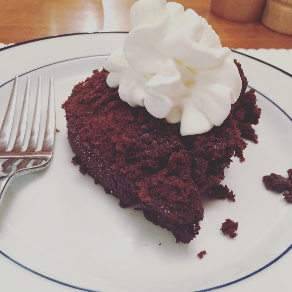 A photo of a slice of the cake with whipped cream on top